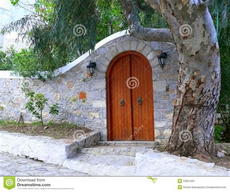 Arched Stone Courtyard Entry Wall With Arched Wooden Door