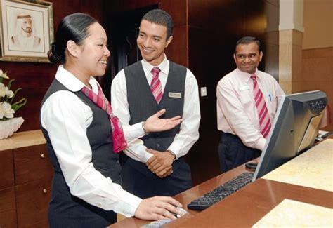 hotel front desk uniforms front desk agents with vests creating behind a desk