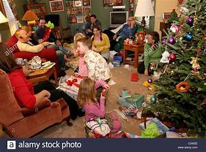 Family opening and giving presents to each other on ...