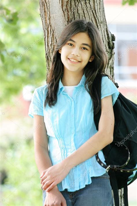 Young Teen Girl Standing With Backpack By Tree Smiling Part As Stock Photo Jarenwicklund