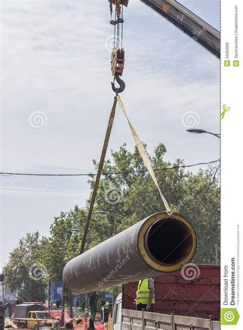 crane hook lifting massive steel pipe stock photo image  isolation moving