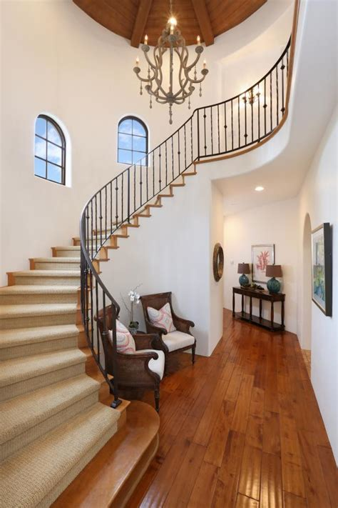 white mediterranean foyer  curved staircase hgtv