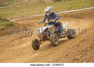 Young male motocross racer riding through dirt track ...