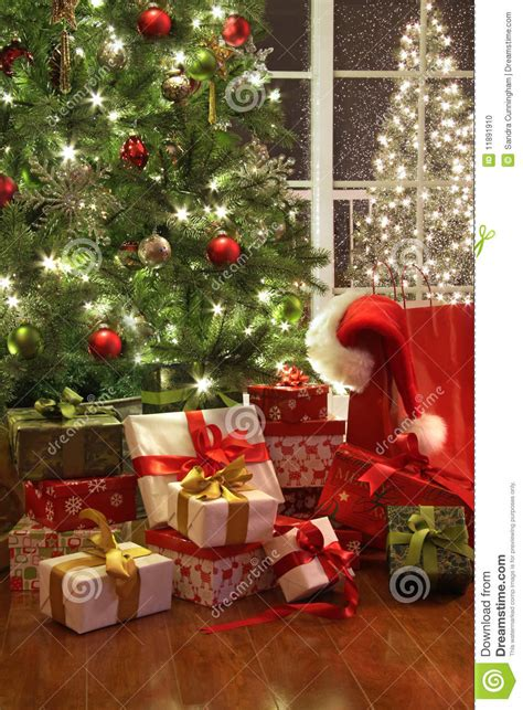 brightly lit christmas tree with lots of gifts stock photo