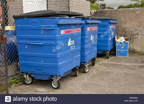 Three Large Blue Plastic Commercial Wheelie Bins Full Of