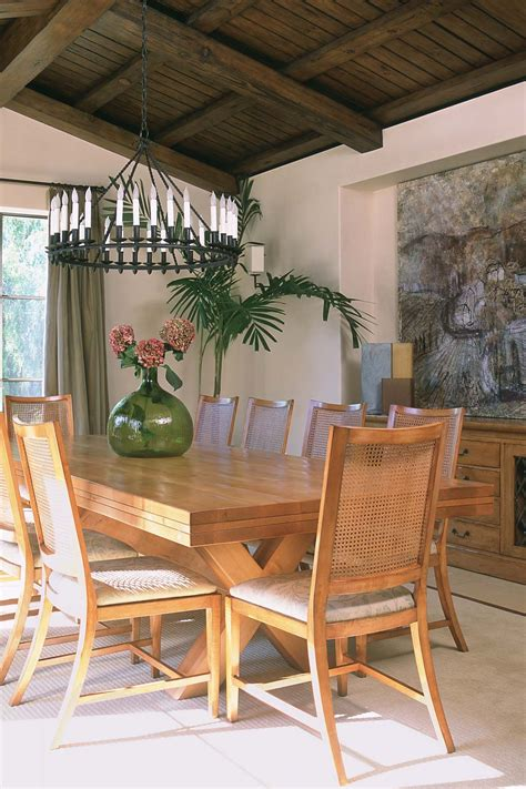 And living stone design + build. Modern rustic dining room with bronze chandelier and woven cane dining chairs. Limestone floors ...