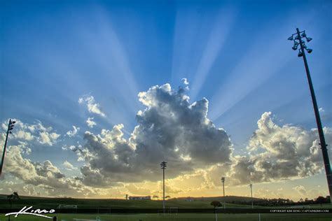Soccer Field Outdoor Sports with Sunrays Clouds in Sky