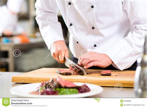 chef cuisine chef in restaurant kitchen preparing food stock photo