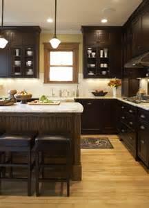 kitchen dark cabinets warm wood floor light counters