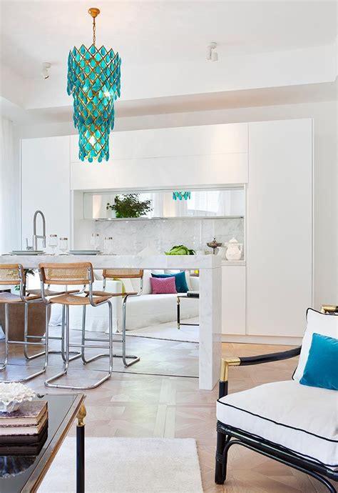 una cocina blanca abierta al salon  una lampara turquesa