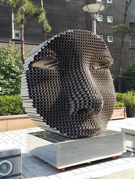 stacked sculpture figurative faces emerge from layers of tightly stacked pipes