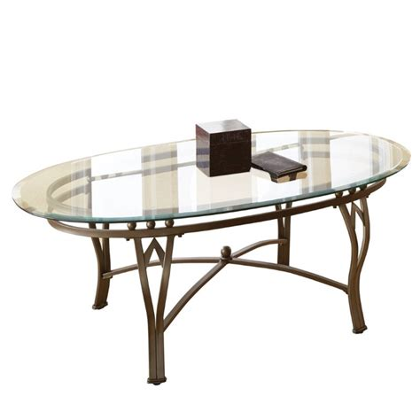This table set showcases great artistry and has a clear glass top. Steve Silver Madrid Oval Glass Top Coffee Table in Weathered Pewter - SR250C-KIT