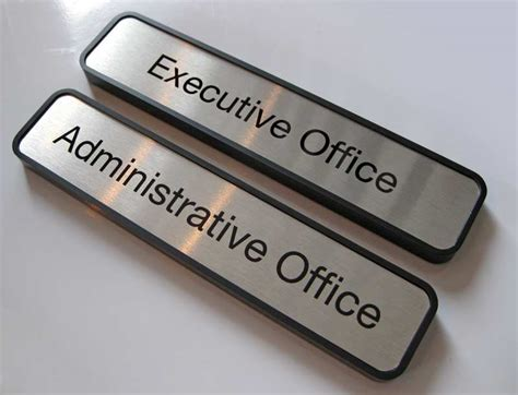 empty cubicles in a modern office building by office door name plates metal office signage