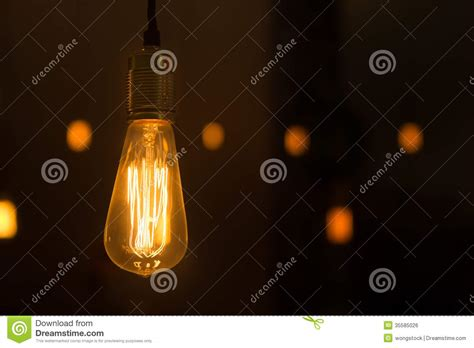 glowing lightbulb dangling from the ceiling royalty free