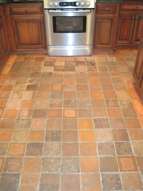 square brown tile kitchen floor combined with brown wooden cabinet with silver stove oven