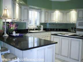 white washed cabinets design and green wall and dramatic black countertops in modern kitchen
