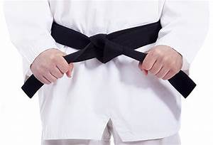 Martial arts man tying his black belt, isolated on white ...