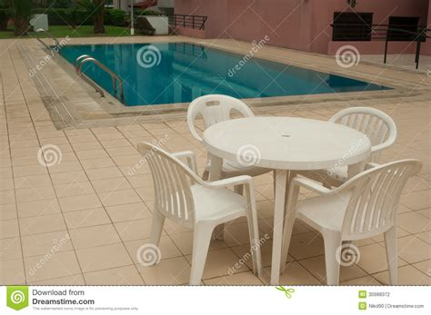chairs and table beside swimming pool inside the aparment