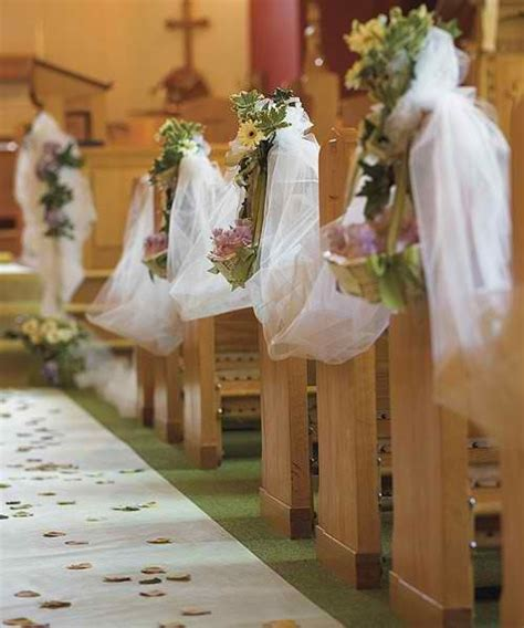 wedding ceremony inside a church isle decor tulle fabric with floral arrangements on the pews