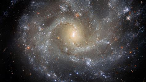 Mirando profundamente en el universo, el telescopio espacial hubble capta un vistazo de las numerosas estructuras en los brazos que se extienden alrededor de esta. نظرة على الكون من خلال تلسكوب هابل الفضائي