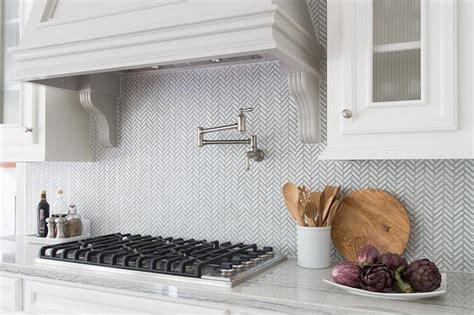 white herringbone backsplash white and gray kitchen with chevron counter stools transitional kitchen