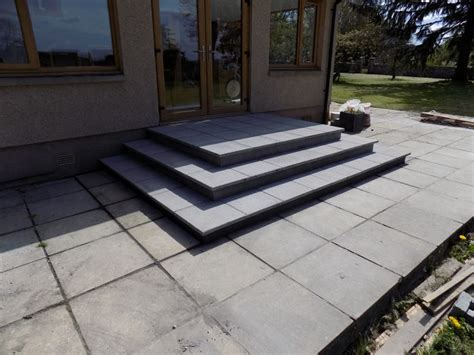 concrete paving slab steps up to a patio door steps