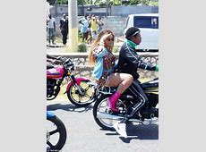 Beyonce sits on the back of a motorcycle driven by Jay Z