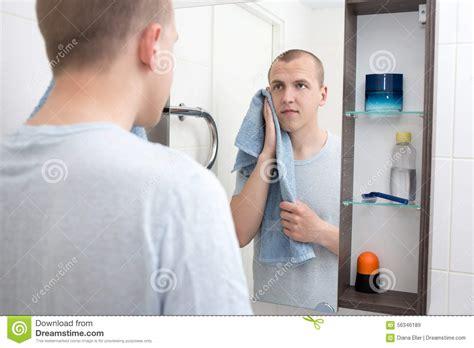 homme ras 233 regardant le miroir dans la salle de bains photo stock image 56346189