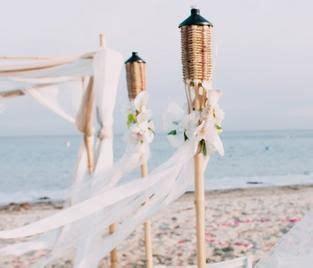 tiki torches lining  aisle   beach wedding
