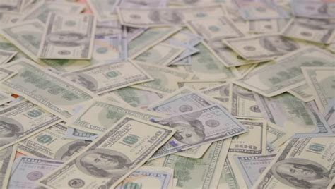 Gun Bullets Falling Onto A Pile Of Hundred Dollar Bills