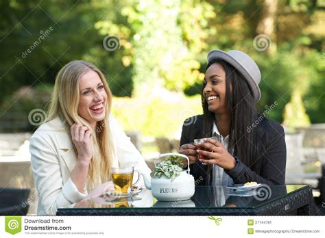multicultural friends laughing  drinking tea stock