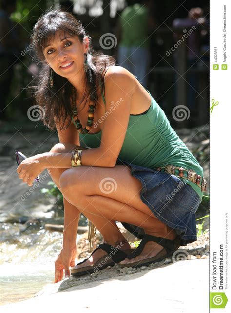 young woman sitting watching  slight smile stock photo