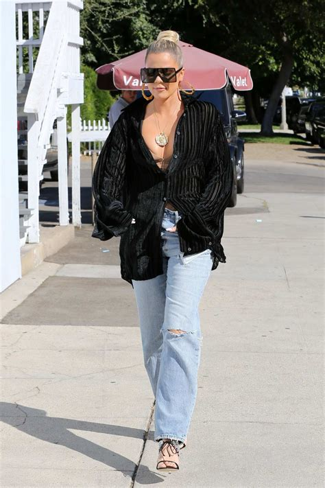 khloe kardashian wears a plunging black shirt and jeans as ...