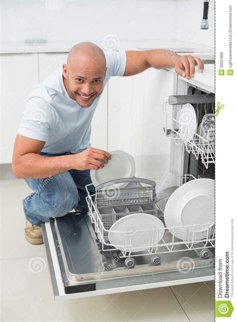 aide de cuisine portrait d 39 un homme de sourire à l 39 aide du lave vaisselle