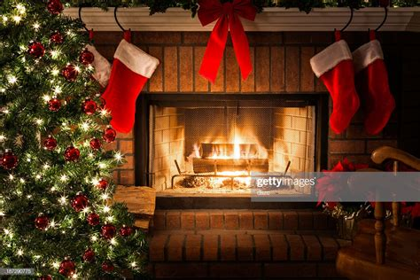 decorated christmas tree blazing fire  fireplace