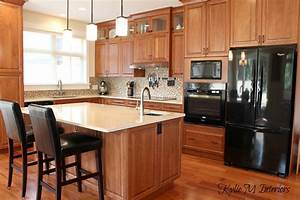 cherry kitchen cabinets in modern transitional kitchen with crema quartz countertops black appliances and exotic wood flooriong with small mosaic tile backsplash 2165