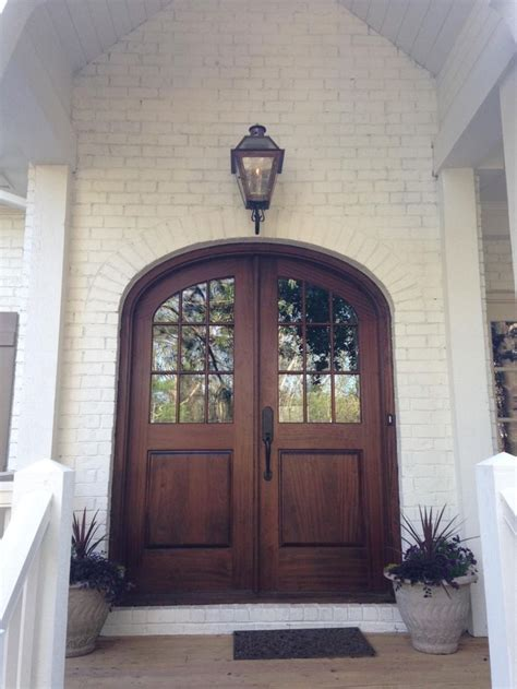 brown arched glass front door  white brick home front