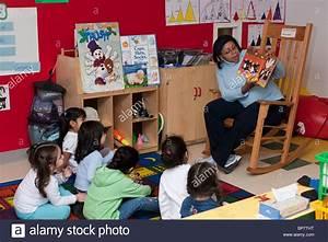 Preschool Classroom Preschool teacher reading a book to ...