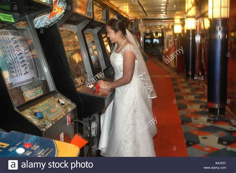 asian bride  wedding gown playing video arcade game