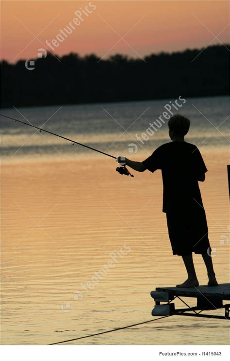 silhouette  young boy fishing  pier stock picture