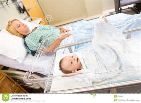 babygirl lying  bassinet  woman  hospital stock