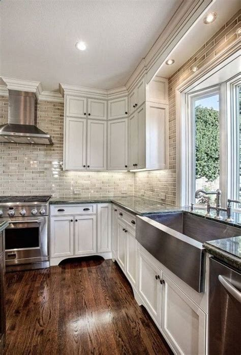 white kitchen cabinets  brick backsplash