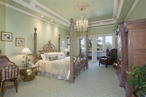 this perpendicular master bedroom features a tray ceiling