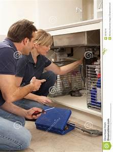 Plumber Teaching Apprentice To Fix Kitchen Sink Stock Photo