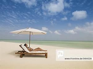 Frau Liegt Auf Sonnenliege Am Strand Lizenzfreies Bild