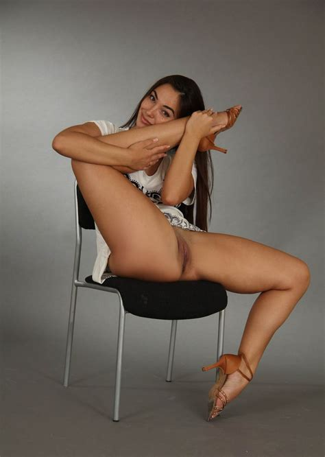 Long Haired Brunette Widely Spreads Her Legs In Studio