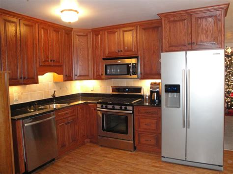 granite countertops and cabinets light oak with white appliances and wood floor slate