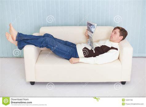 Junger Mann Liest Die Zeitschrift, Die Auf Couch Liegt
