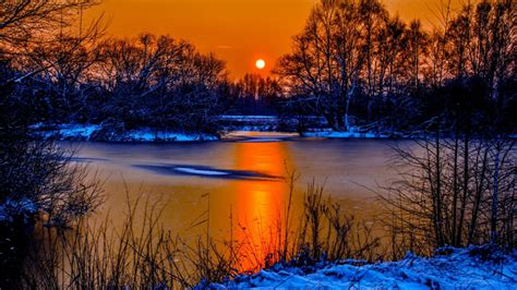 sunset  winter snow river coast  sun orange sky