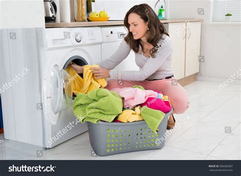 Young Woman Putting Clothes Into Washing Stock Photo